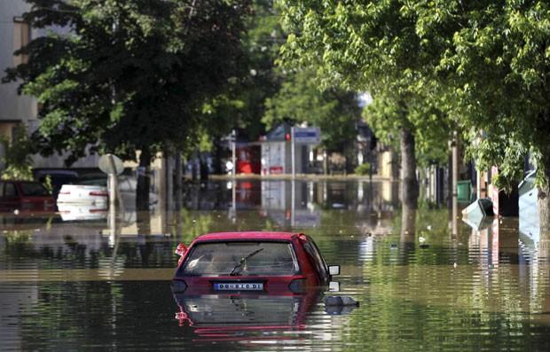 Carro é visto em alagamento na cidade de Obrenovac, na Sérvia, nesta segunda-feira (19) (Foto: Antonio Bronic/Reuters)