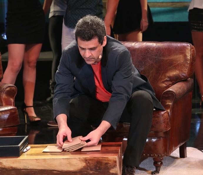 Bruno Garcia embaralha os envelopes com os telefones celulares (Foto: Carol Caminha / Gshow)