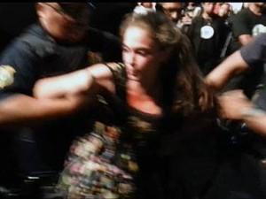 A estudante Joana Palhares, de 18 anos, sendo retirada do evento de Feliciano (Foto: (Foto: Reprodução/Facebook))