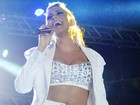 Alinne Rosa joga a blusa para o alto durante show na Bahia