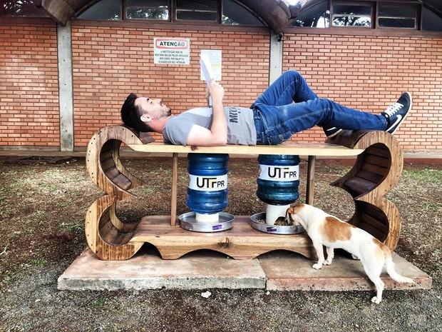Alimentador em formato de osso de madeira instalado em frente ao campus da UTFPR em Medianeira (PR) briga ração e água e serve de ponto de descanso (Foto: AlimentaCão / Divulgação)