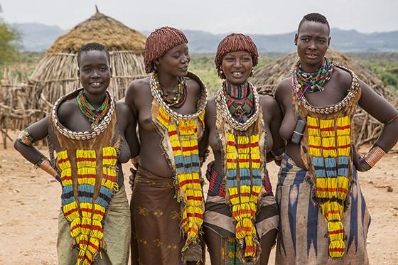 Quatro jovens hamers em seu vilarejo a cerca de 10 km de Turmi vestem suas roupas tradicionais, mas o celular (pendurado na roupa da mulher da direita) começa a aparecer na foto (Foto: © Haroldo Castro/ÉPOCA)