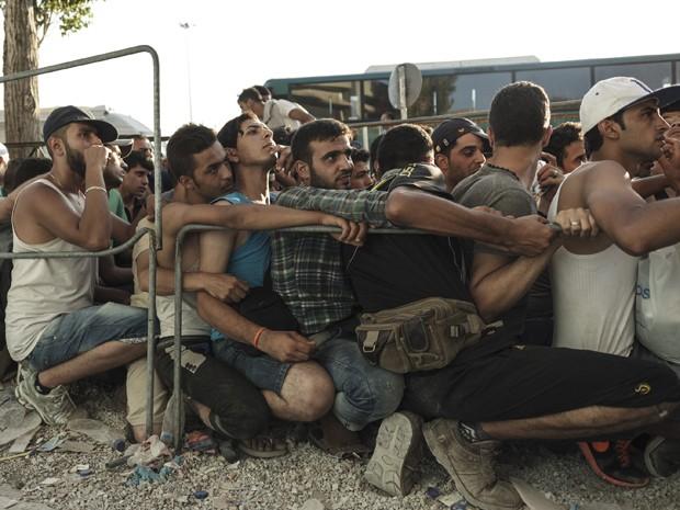 Imigrantes aguardam para se registrarem perante as autoridades de Mytilene, na ilha grega de Lesbos, na segunda (17) (Foto: AFP Photo/Achilleas Zavallis)