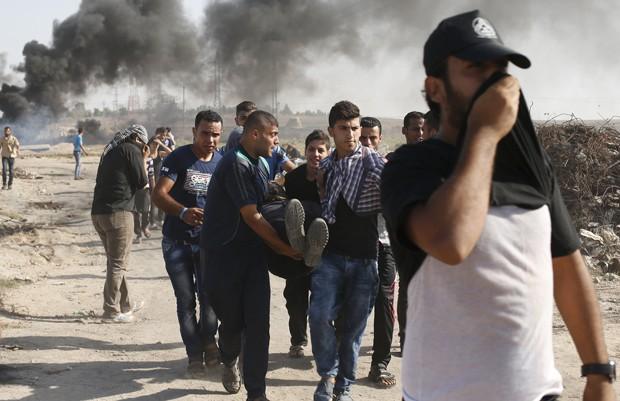 Palestino ferido é retirado por manifestantes durante em confronto no leste da Faixa de Gaza, nesta sexta-feira (16) (Foto: Suhaib Salem/ Reuters)
