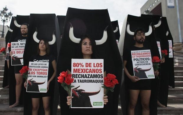 Ativistas usaram chifres e simularam estar em caixões fictícios durante protesto contra touradas no México (Foto: Reuters/Stringer)