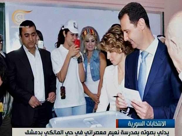 Imagem reproduzida da TV 'Al-Mayadeen', do Líbano, mostra o presidente sírio, Bashar al-Assad e sua mulher, Asmaa, votando em um posto eleitoral em Maliki, no Centro de Damasco. (Foto: TV Al-Mayadeen / Via AFP Photo)