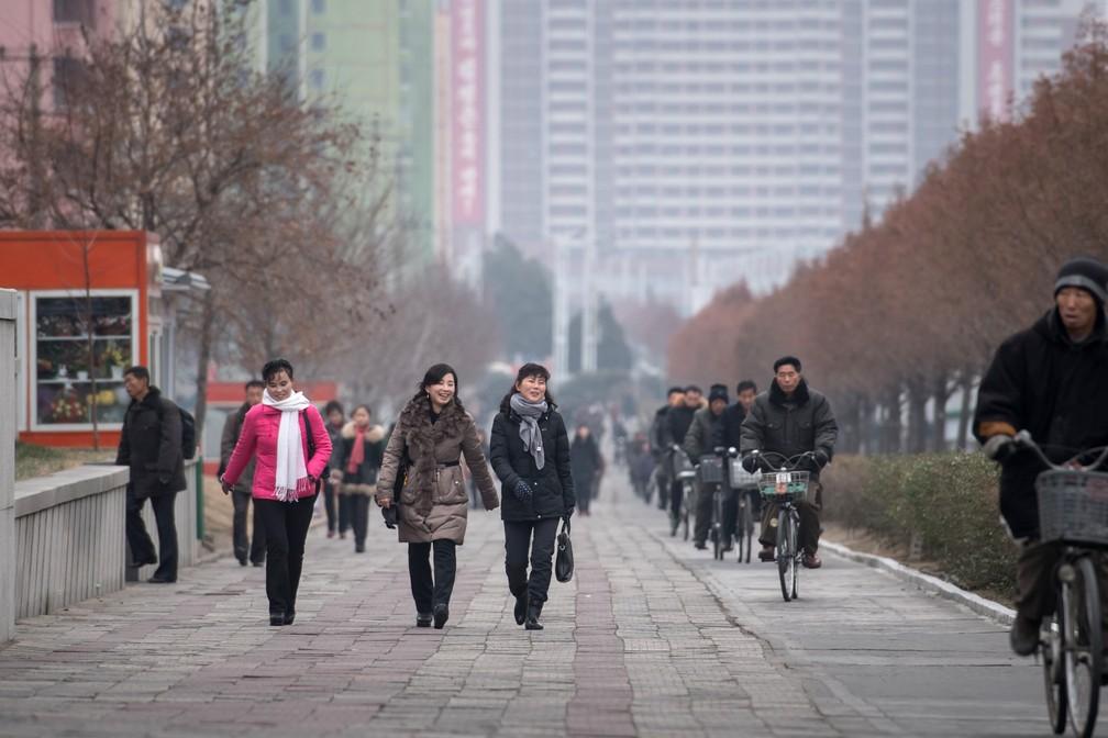 Norte-coreanos vão ao trabalho numa manhã de novembro em Pyongyang (Foto: Ed Jones/AFP)
