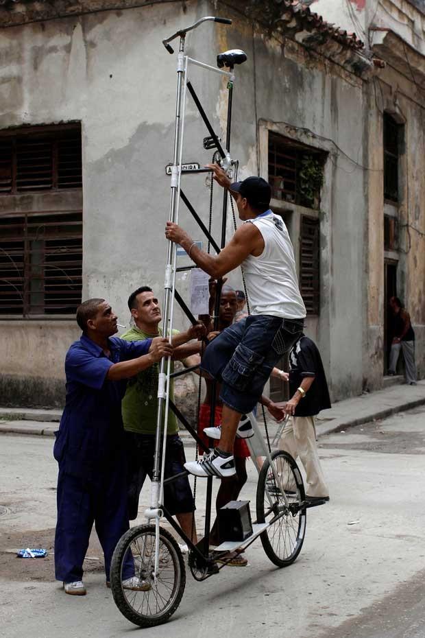Felix Guirola precisa de ajuda para subir na bicicleta. (Foto: Franklin Reyes/AP)