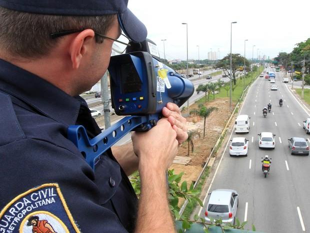 Integrante da Guarda Civil Metropolitana (GCM) fiscaliza velocidade de motos que circulam pela Marginal Tietê, da Ponte do Limão, na Zona Norte de São Paulo, com o auxílio de um radar pistola. Pelo menos 10 radares móveis irão flagrar motociclistas (Foto: Werther Santana/Estadão Conteúdo)