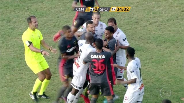 <p>  Fabrício coloca bola pra fora para atendimento a Júnior Lemos e Rithely vai reclamar com o lateral. Jogadores do Central não gostam da atitude de Rithely e vão pra cima dele.</p>