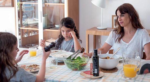 3. A protagonista tenta atender os pedidos das meninas em um almoço particularmente caótico (Foto: Priscila Prade)