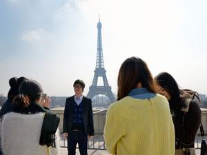 Turistas chineses tiram foto em frente à Torre Eiffel, em Paris (Foto: Eric Feferberg/AFP)
