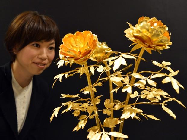 Funcionária da loja que realiza a 'Gold Expo' observa flores feitas em ouro. Arranjo, de 4,2 kg, custa R$ 3,4 milhões (Foto: Yoshikazu Tsuno/AFP)