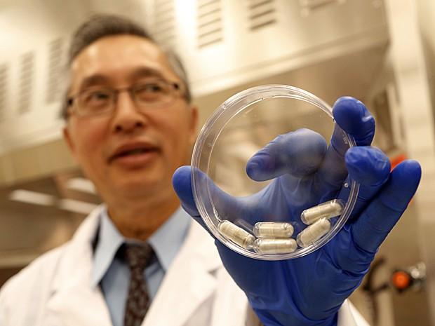 Especialista em doenças infecciosas Thomas Louie mostra cápsulas em gel com fezes em seu laboratório em Calgary, no Canadá. Comprimidos podem substituir transplantes fecais para tratar infecções (Foto: The Canadian Press, Jeff McIntosh/AP)