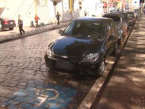Carro sem credencial ocupa parte da vaga de deficiente em Araraas (Foto: César Fontenele / EPTV)
