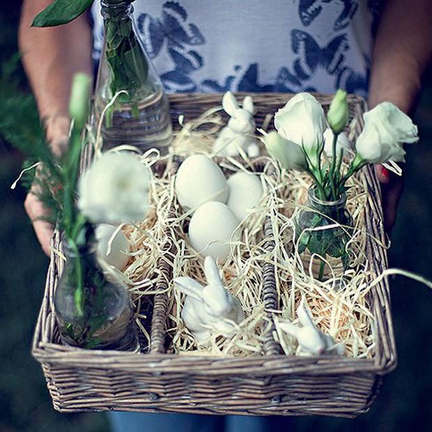 Sabe aquele porta-talheres de vime, todo sem graça? Com palha, ovos cozidos, coelhos de louça e flores em garrafas, ele vira um centro de mesa encantador. (Foto: Rogério Voltan/Casa e Comida)