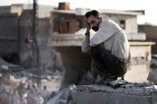 Sírio observa área onde foram destruídas ao menos dez casas na cidade de Azaz (Foto: AP Photo/Shaam News Network, SNN)