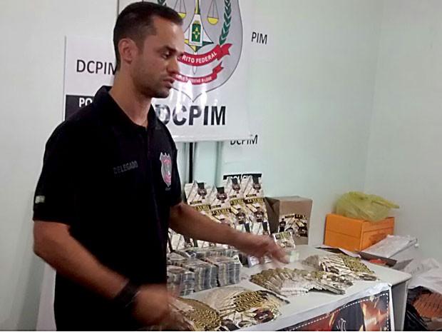 """O delegado Luiz Henrique Dourado Sampaio, da DCPIM, ao lado de material de divulgação de """"banda falsa"""" (Foto: Isabella Calzolari/G1)"""