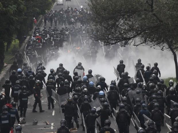 Policiais seguem para enfrentar manifestantes perto do aeroporto da Cidade do México (Foto: AP Photo/Marco Ugarte)