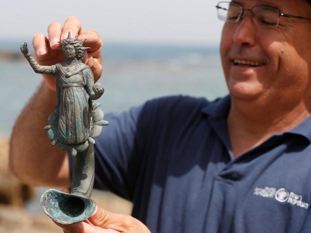 Funcionário do departamento responsável por antiguidades em Israel segura estátua de cerca de 1,6 mil encontrada em navio mercante que afundou próximo do antigo porto da Cesarea, em Israel  (Foto: Baz Ratner/Reuters)