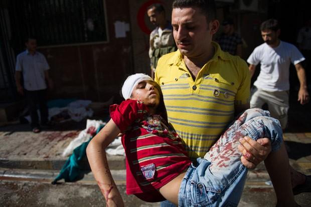 Homem carrega menino ferido em ataque das forças do regime sírio em Aleppo, na sexta-feira (10) (Foto: Phill Moore / AFP)