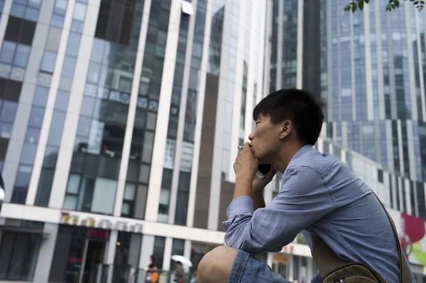 Homem é visto fumando em Pequim nesta segunda-feira (1º). Lei que proíbe o fumo em lugares públicos fechados entrou em vigor na cidade  (Foto: Fred Dufour/AFP)
