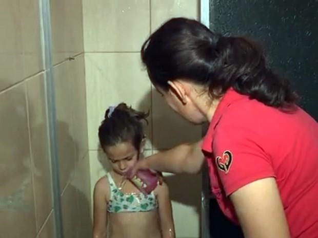 A auxiliar de padaria, Jerusa Cardoso, tem que dar banho nos filhos com água do galão. (Foto: Reprodução EPTV/ Marcelo Rodrigues)