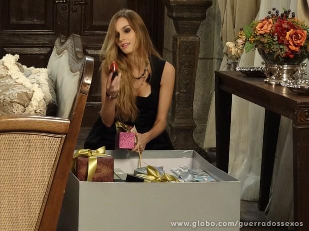 Analú pega a boneca para fazer mandinga (Foto: Guerra dos Sexos/TV Globo)