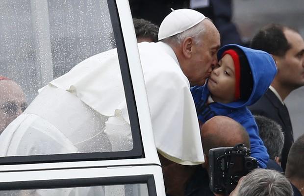 Papa beija criança durante passagem de papamóvel pelo exterior da Basílica de Aparecida (Foto: AP Photo/Victor R. Caivano)