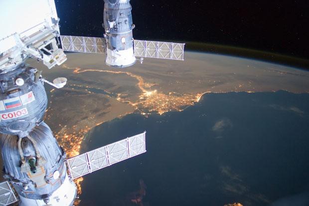 Imagem divulgada pela Nasa mostra o Oriente Médio à noite, fotografago por um dos integrantes da expedição 31 a bordo da Estação Espacial Internacional. A foto foi feita em 4 de junho, a uma distância de cerca de 400 quilômetros sobre o Mar Mediterrâneo. Nela, pode-se ver o delta do Rio Nilo ao centro, e as luzes das cidades do Cairo e de Alexandria. Duas espaçonaves russas atracadas na estação também aparecem: a Soyuz (à esquerda) e a Progress (Foto: Nasa/AP)