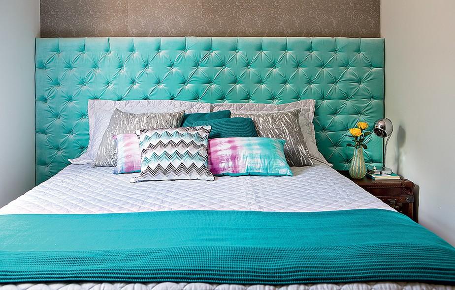 Turquesa, o veludo forra a cabeceira da cama. Almofadas e manta seguem o tom. Projeto da arquiteta Letícia Arcangeli