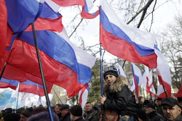 Menino segurando bandeira russa é visto durante evento pelo aniversário da saída da Crimeia da Ucrânia nesta segunda-feira (16) em Simferopol (Foto: Max Vetrov/AFP)