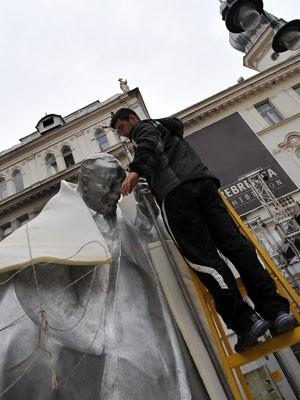 Funcionário retira capa protetora da estátua do Papa João Paulo II em Sarajevo (Foto: Elvis Barukcic/AFP)