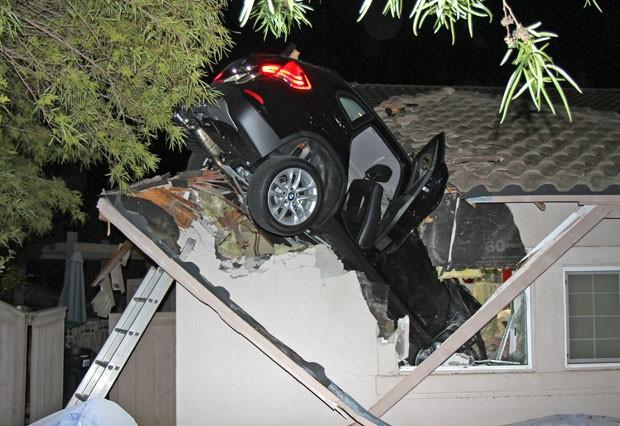 Motorista de BMW perdeu controle da direção e foi parar no telhado de casa (Foto: George Strother/AP)