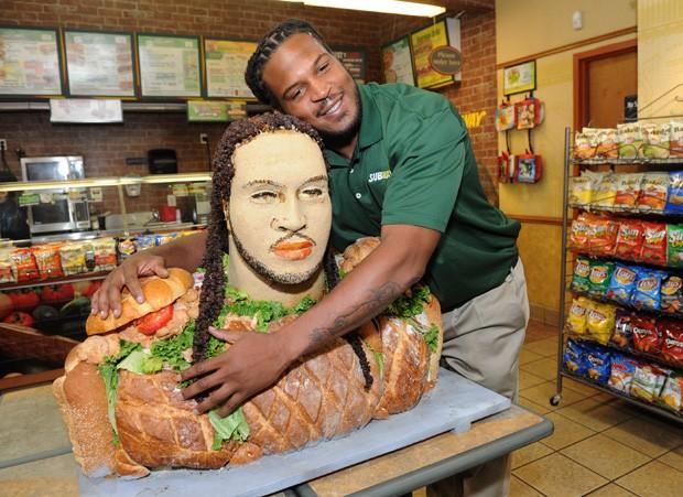 Jarvis Jones abraça busto feito de sanduíche em franquia de rede de fast food (Foto: Diane Bondareff/AP)