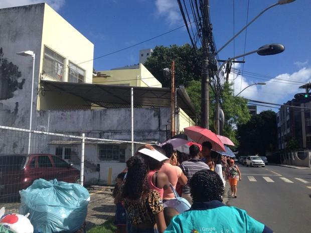 População tenta se proteger do sol em fila de posto no bairro da Federação (Foto: Juliana Almirante/ G1)