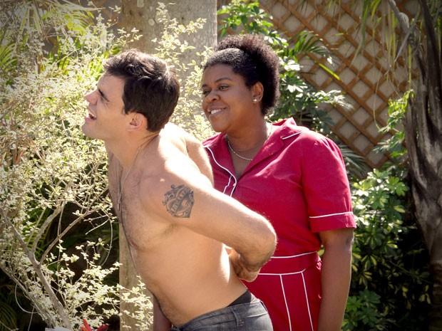 A empregada capricha na masageme  faz o bonitão se curvar (Foto: Avenida Brasil/TV Globo)