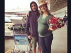 Pedro Scooby recebe Luana Piovani com flores em aeroporto