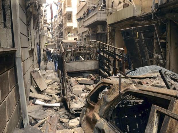 Sírios se reúnem em uma rua destruída por uma bomba em Aleppo, na Síria (Foto: Sana/AP)