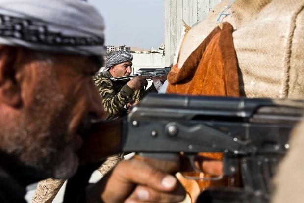 Combatentes do Exército da Síria Livre e das Unidades de Proteção do Povo Curdo se uniram para se defender dos extremistas do grupo Estado Islâmico, em Kobani (Foto: Jake Simkin/AP)