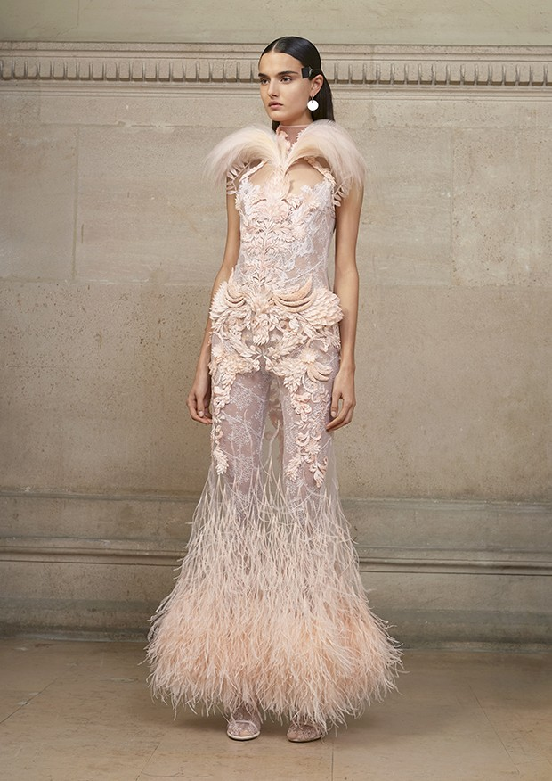 Blanca wears an illusion-tulle dress embellished with rooster, ostrich and intricately-cut feathers, topped with a pink birds-of-paradise plume delicately framing the face; worn with a lace-encrusted patchworked jumpsuit GIVENCHY (Foto: Givenchy)