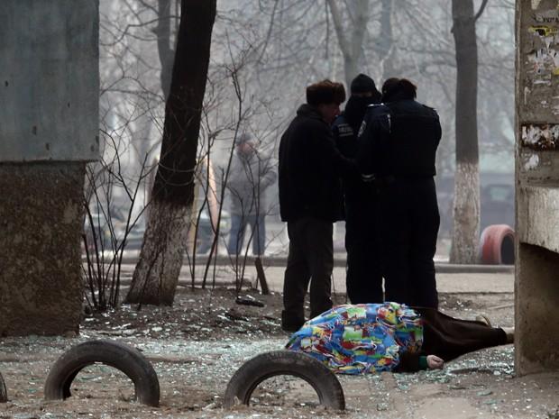 Policiais se reúnem ao lado de um corpo coberto depois de bombardeio na cidade portuária de Maiupol, na Ucrânia, neste sábado (24) (Foto: Stringer/AFP)