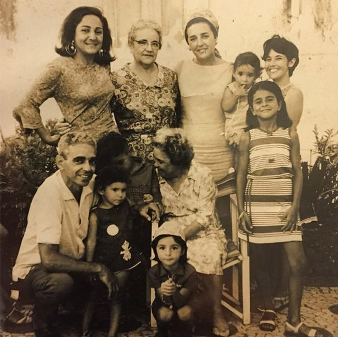 Foto antiga de Daniela Mercury com a família. Cantora está no canto superior direito, no colo da mãe, Liliana. No canto esquerdo, o pai, Antonio, com os irmãos de Daniela, Tom e Kity (Foto: Arquivo pessoal)