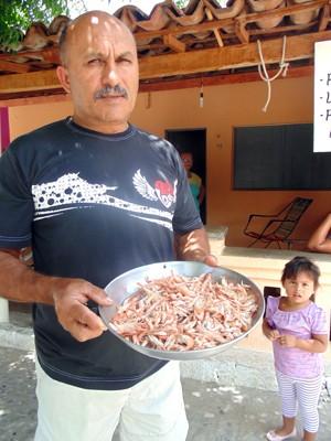Francisco Medeiros, o Titi, mostra o pouco do camarão que conseguiu pegar (Foto: Anderson Barbosa/G1)
