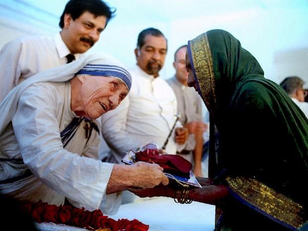 Madre Teresa apresenta documentos de uma nova casa a uma moradora de Bombai, na Índia, em 1994 (Foto: Savita Kirloskar)