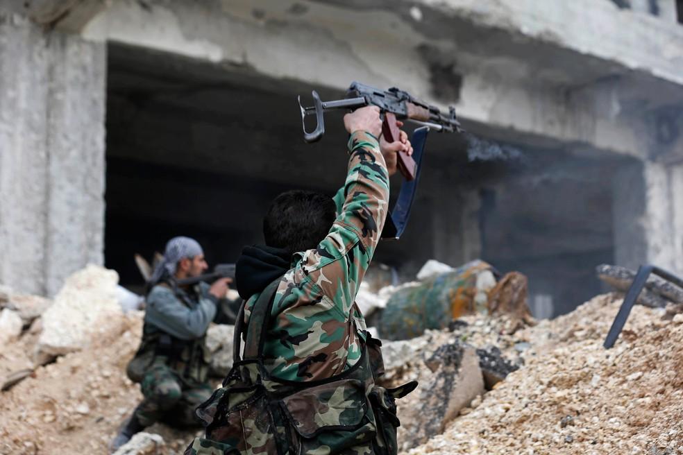 Soldados do exército sírio disparam suas armas durante uma batalha em Ramouseh, leste de Aleppo. (Foto: AP Photo/Hassan Ammar)