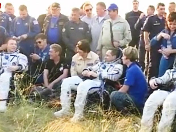 Os astronautas sentados após resgate da cápsula, no Cazaquistão (Foto: Reprodução/TV Nasa/Roscosmos)