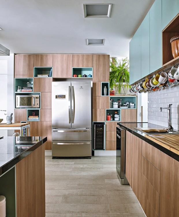 O armário na cozinha reúne nichos de diferentes tamanhos, revestidos pelo mesmo tom de laca usado em outros espaços (Foto: Victor Affaro / Editora Globo)
