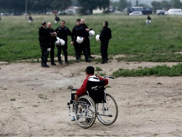 Criança em cadeira de rodas sai do campo de Idomeni; ao fundo, policiais supervisionam a operação (Foto: Yannis Kolesidis/AP)