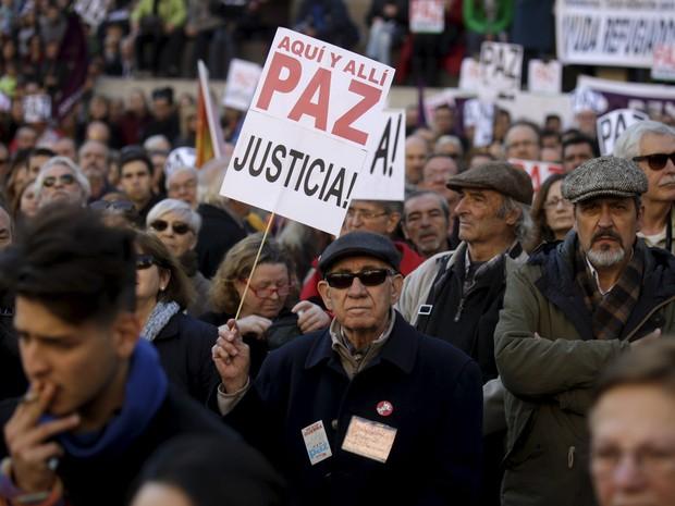 Um homem exibe um cartaz pedindo paz e justiça durante um protesto em Madri, na Espanha, contra ataques militares e bombardeios na Síria (Foto: Andrea Comas/Reuters)